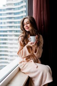 Giovane donna fresca in accappatoio rosa tenero beve il tè, guardando fuori dalla finestra.