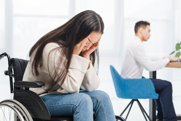 Giovane donna frustrata che soffre dall'emicrania che si siede sulla sedia a rotelle davanti all'uomo d'affari che lavora nell'ufficio