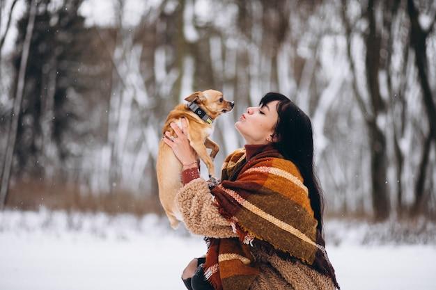 Giovane donna fuori dal parco con il suo cagnolino in inverno