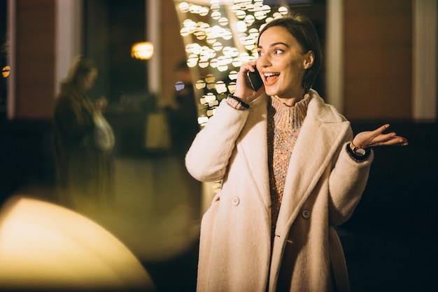 Giovane donna fuori dalla strada di notte con luci