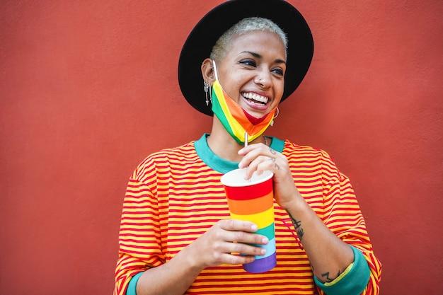Giovane donna gay che beve da un bicchiere arcobaleno durante l'evento di orgoglio