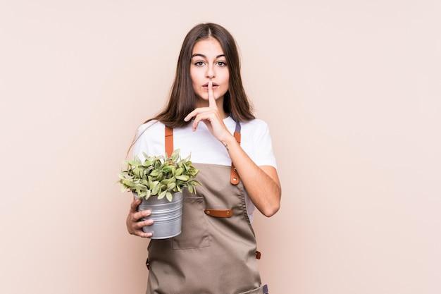 Giovane donna giardiniere in possesso di un plantkeeping un segreto o chiedere silenzio