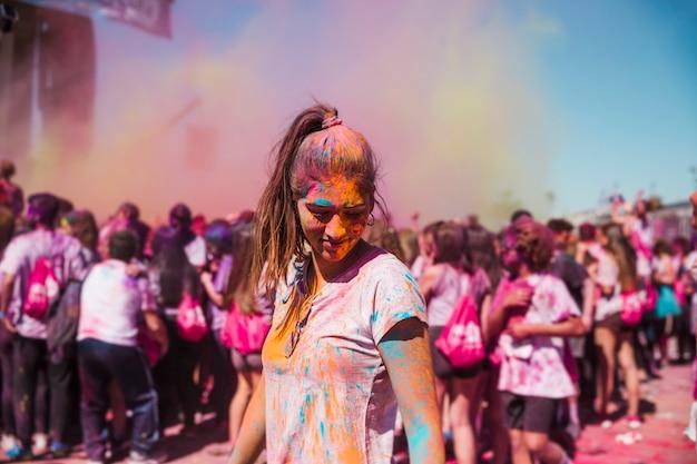 Giovane donna godendo con colori holi nella folla