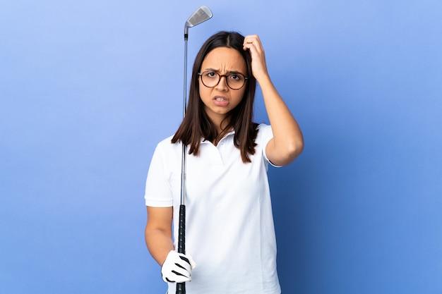 Giovane donna golfista sul muro colorato con un'espressione di frustrazione e non comprensione