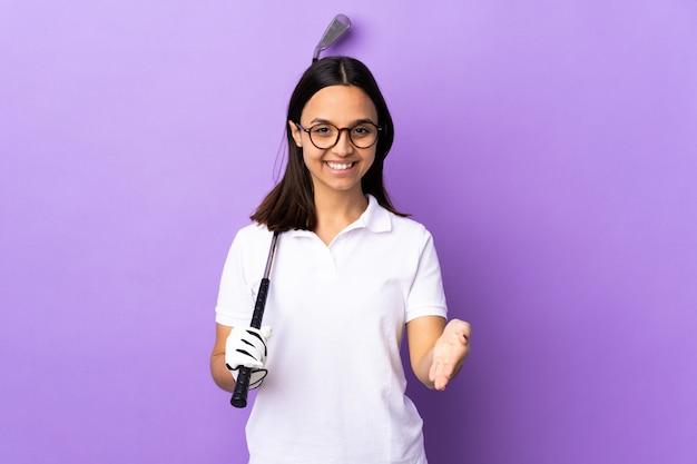 Giovane donna golfista sul muro colorato si stringono la mano per chiudere un buon affare