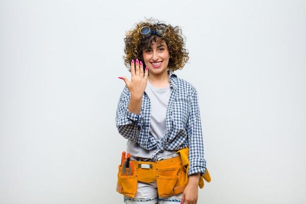 Giovane donna governante sorridente e guardando amichevole, mostrando il numero cinque o quinto con la mano in avanti, il conto alla rovescia sul muro bianco