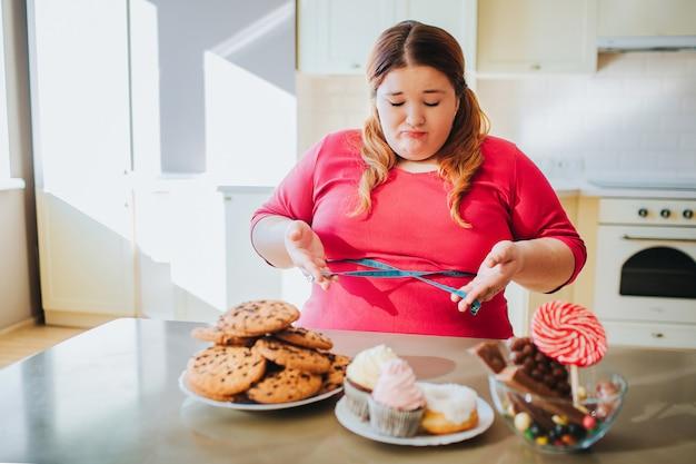 Giovane donna grassa in cucina che si siede e che mangia alimento dolce.