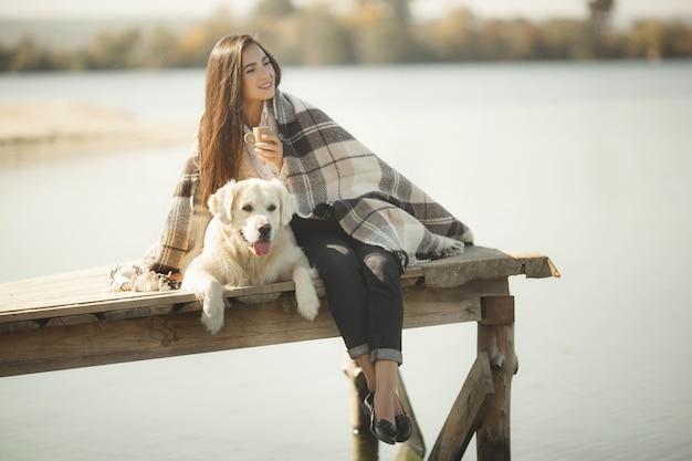 Giovane donna graziosa all'aperto con il cane. golden retriever e il suo proprietario che riposano vicino all'acqua e bevono tè