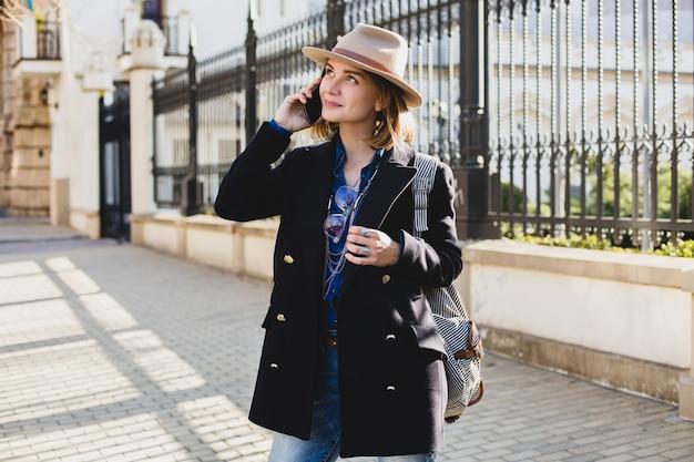Giovane donna graziosa alla moda che sorride e che parla sul suo telefono, vestita in jeans e cappotto blu scuro