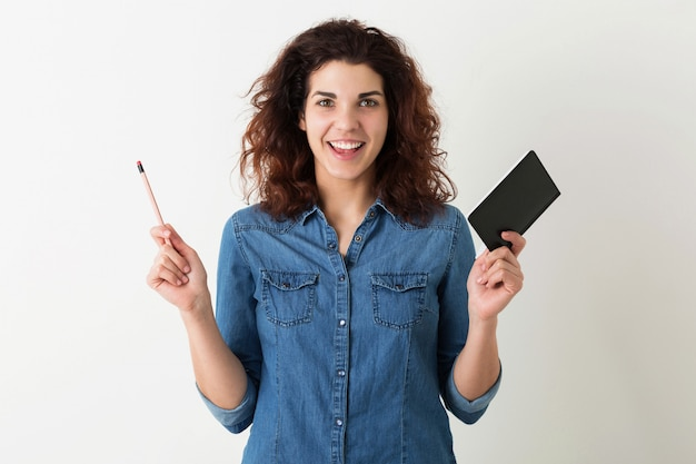 Giovane donna graziosa, alzando le mani con il taccuino e la matita, sorridente, espressione del viso sorpreso, capelli ricci, emozione positiva, felice, isolato, camicia blu denim, studente, educazione