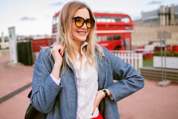 Giovane donna graziosa bionda che cammina al centro di londra, indossando abiti da studente casual elegante elegante, cappotto blu e occhiali colorati, tempo di mezza stagione autunno primavera, umore itinerante.