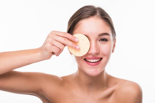 Giovane donna graziosa che applica fard sul suo fronte con il soffio di polvere isolato sulla parete bianca