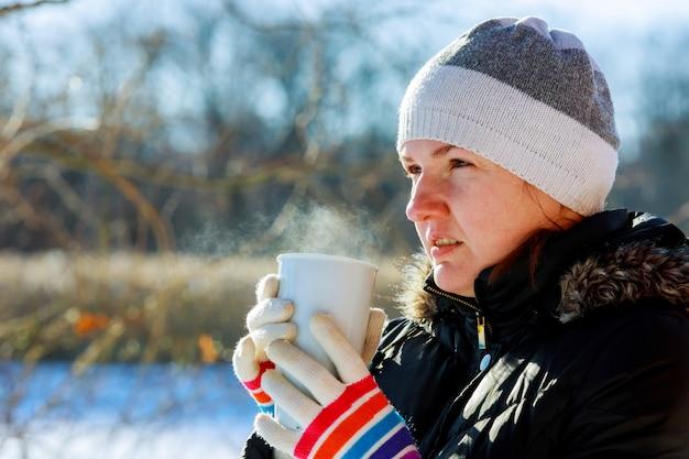 Giovane donna graziosa che beve tè caldo un giorno di inverno freddo