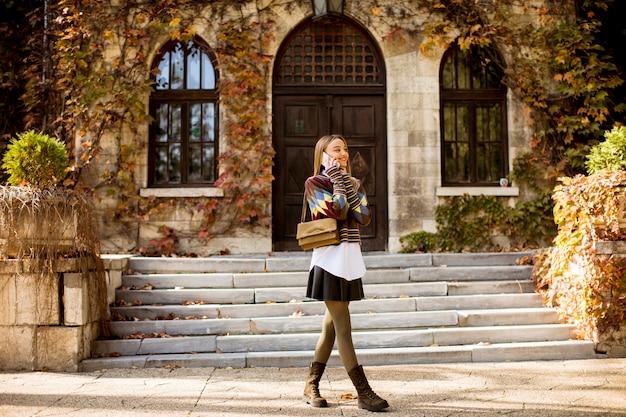 Giovane donna graziosa che cammina nel parco di autunno