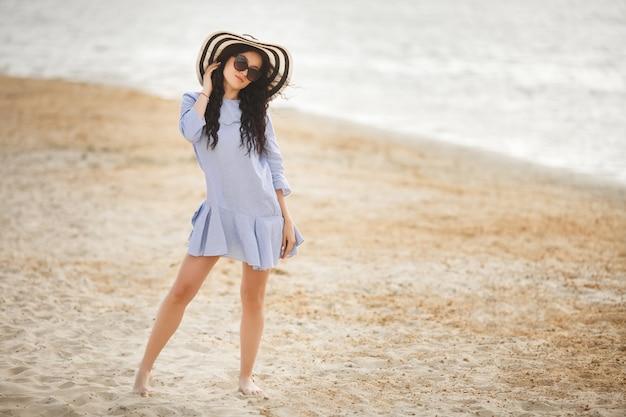 Giovane donna graziosa che cammina su una spiaggia. ragazza adulta attraente vicino al rilassamento dell'acqua. bella donna sul mare