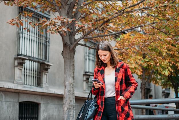 Giovane donna graziosa che cammina sulla strada facendo uso del telefono