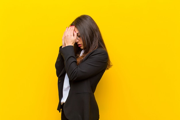 Giovane donna graziosa che copre gli occhi con le mani con uno sguardo triste e frustrato di disperazione, pianto, vista laterale sulla parete arancione