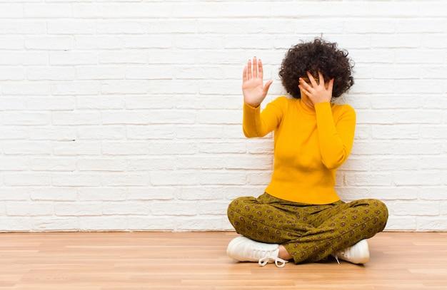 Giovane donna graziosa che copre il viso con la mano e mettendo l'altra mano in alto per fermare la fotocamera, rifiutando foto o immagini seduti sul pavimento