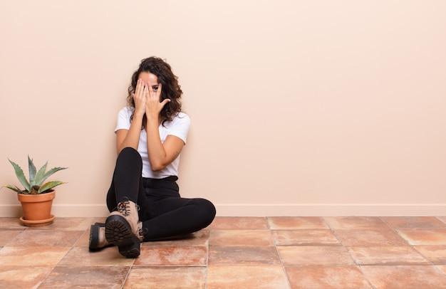 Giovane donna graziosa che copre il viso con le mani, sbirciando tra le dita con espressione sorpresa e guardando al lato seduto un pavimento della terrazza