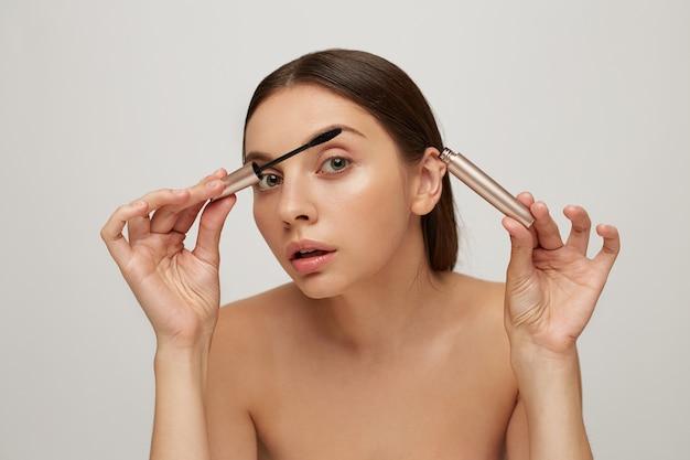 Giovane donna graziosa che dipinge ciglia con mascara