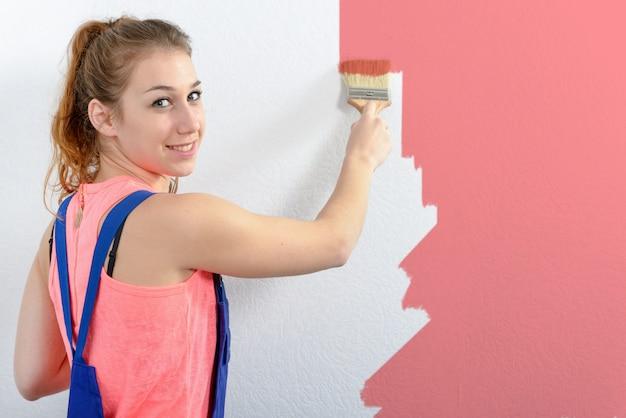 Giovane donna graziosa che dipinge il colore rosa della parete
