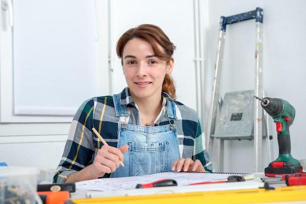 Giovane donna graziosa che fa lavoro di diy a casa