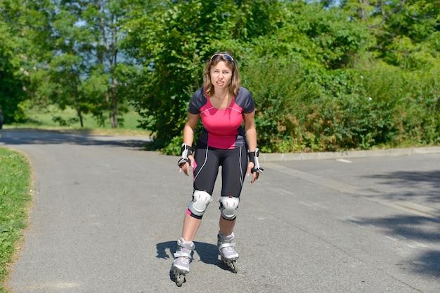 Giovane donna graziosa che fa pattino a rotelle su una pista