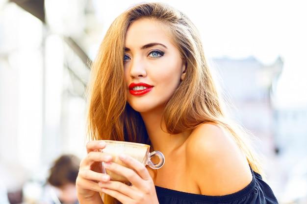 Giovane donna graziosa che gode, che beve tazza di cappuccino, latte, caffè in caffè di strada di mattina.