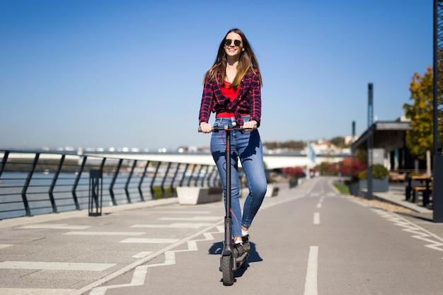 Giovane donna graziosa che guida un motorino elettrico nella via