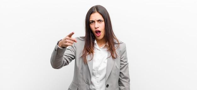 Giovane donna graziosa che indica con un'espressione aggressiva arrabbiata che sembra un capo furioso e pazzo