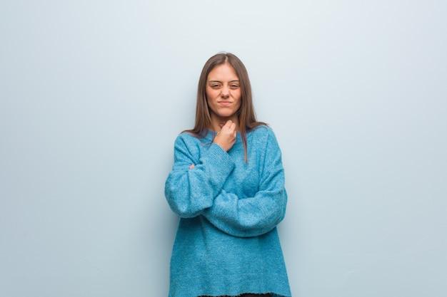 Giovane donna graziosa che indossa un maglione blu tosse, malato a causa di un virus o infezione