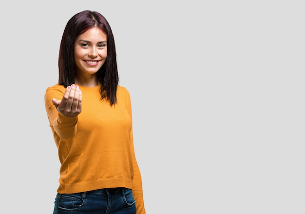 Giovane donna graziosa che invita a venire, sicuro e sorridente che fa un gesto con la mano