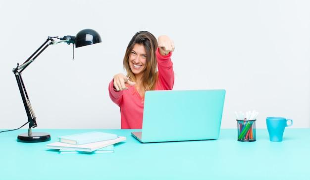 Giovane donna graziosa che lavora con un computer portatile che ritiene felice e sicuro che indica la macchina fotografica con entrambe le mani e che ride scegliendo voi