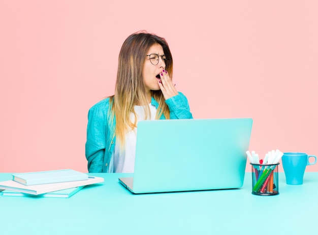 Giovane donna graziosa che lavora con un computer portatile che sbadiglia pigramente nelle prime ore del mattino, svegliarsi e sembrare assonnato, stanco e annoiato