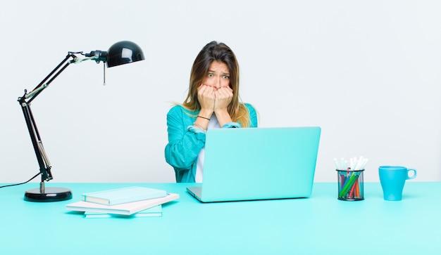 Giovane donna graziosa che lavora con un computer portatile che sembra le unghie preoccupate, ansiose, sollecitate e impaurite e mordaci e che guardano al copyspace laterale