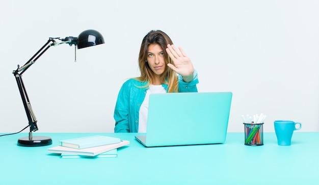 Giovane donna graziosa che lavora con un computer portatile che sembra palma aperta di rappresentazione seria, severa, dispiaciuta e arrabbiata che fa gesto di arresto