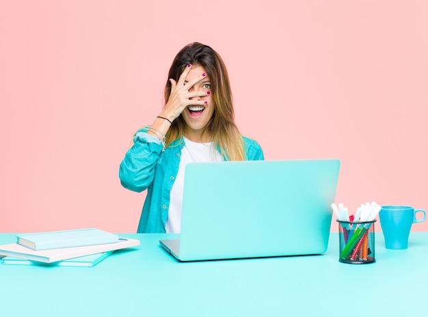 Giovane donna graziosa che lavora con un computer portatile che sembra scioccato, spaventato o terrorizzato, coprendo il viso con la mano e sbirciando tra le dita