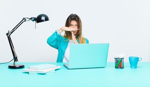 Giovane donna graziosa che lavora con un computer portatile che sembra serio