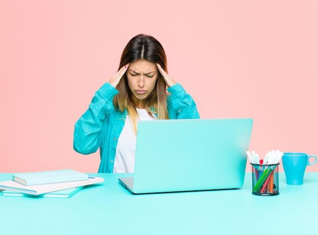 Giovane donna graziosa che lavora con un computer portatile che sembra stressato e frustrato, che lavora sotto pressione con un mal di testa e turbato da problemi