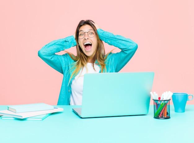 Giovane donna graziosa che lavora con un computer portatile che solleva le mani alla testa, a bocca aperta, sentendosi estremamente fortunato, sorpreso, eccitato e felice