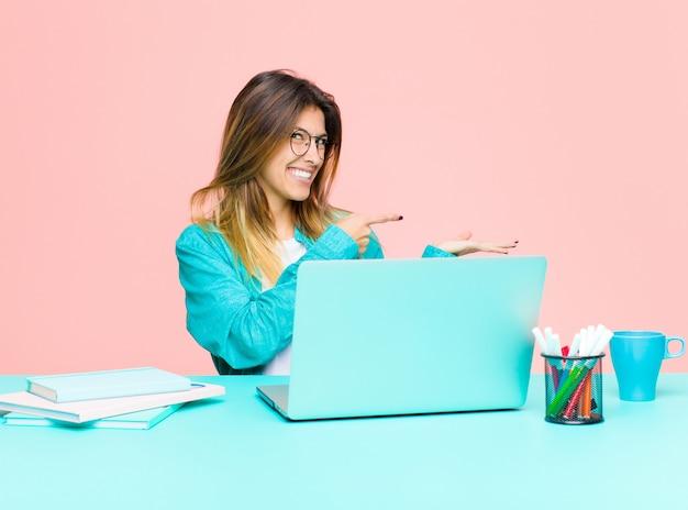 Giovane donna graziosa che lavora con un computer portatile che sorride allegramente e che indica lo spazio della copia sulla palma dal lato che mostra o che annuncia un oggetto