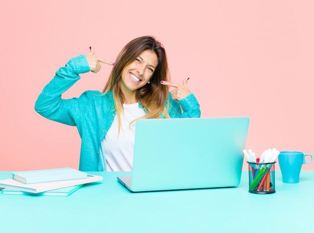 Giovane donna graziosa che lavora con un computer portatile che sorride con confidenza indicando il proprio ampio sorriso, atteggiamento positivo, rilassato, soddisfatto