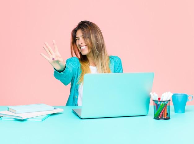 Giovane donna graziosa che lavora con un computer portatile che sorride e che sembra amichevole, mostrando numero quattro o quarto con la mano in avanti, conto alla rovescia