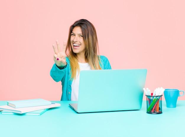 Giovane donna graziosa che lavora con un computer portatile che sorride e che sembra amichevole, mostrando numero threethird con la mano in avanti, conto alla rovescia