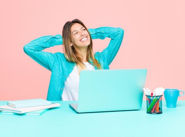 Giovane donna graziosa che lavora con un computer portatile che sorride e che si sente rilassato, soddisfatto e spensierato, ridendo positivamente e raffreddando