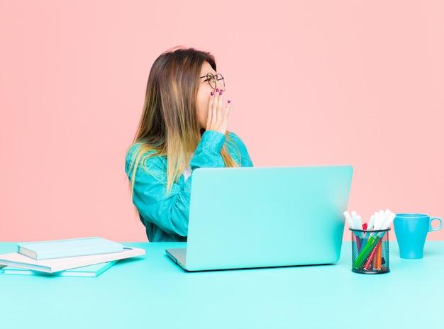 Giovane donna graziosa che lavora con un computer portatile che urla ad alta voce e con rabbia per copiare lo spazio sul lato, con la mano accanto alla bocca
