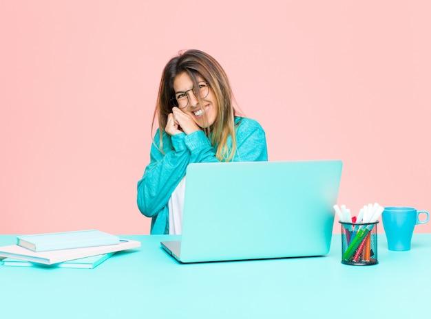 Giovane donna graziosa che lavora con un computer portatile sentirsi innamorati e che sembra carino, adorabile e felice, sorridendo romanticamente con le mani accanto al viso