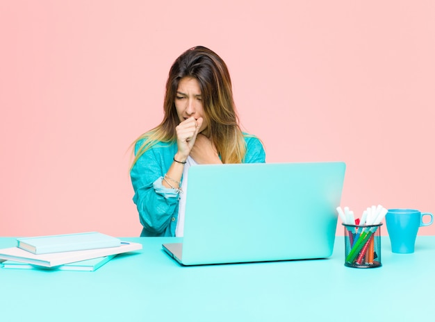 Giovane donna graziosa che lavora con un computer portatile sentirsi male con mal di gola e sintomi influenzali, tossendo con la bocca coperta