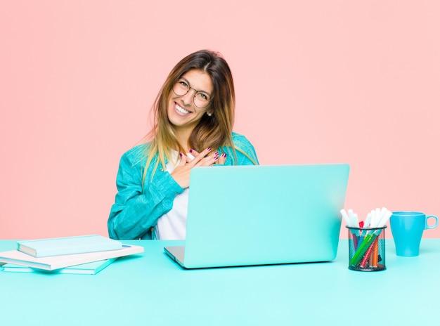 Giovane donna graziosa che lavora con un computer portatile sentirsi romantico, felice e innamorato, sorridendo allegramente e tenendosi per mano vicino al cuore