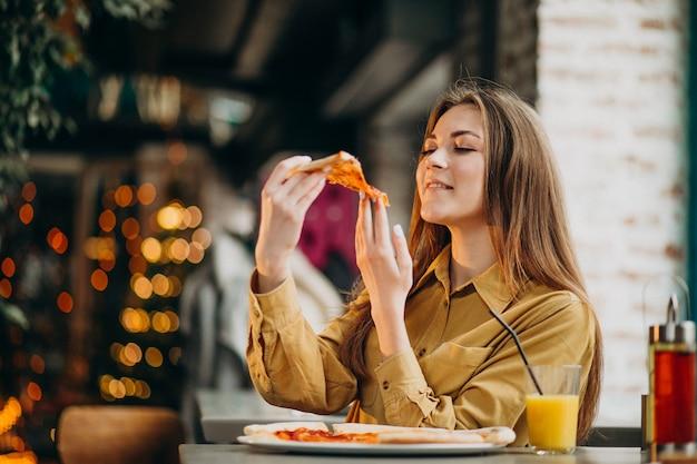 Giovane donna graziosa che mangia pizza in un bar